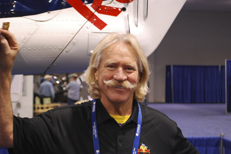 Chuck Aaron standing next to his helicopter at Heli-Expo 2014.